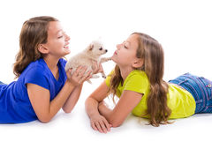 Happy twin sister kid girls and puppy dog lying. Playing on white background stock photos