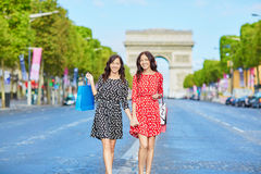 Happy twin sisters doing shopping on holidays in France Royalty Free Stock Images