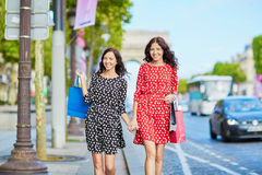 Happy twin sisters doing shopping on holidays in France Stock Image