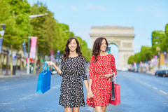 Happy twin sisters doing shopping on holidays in France Royalty Free Stock Photography