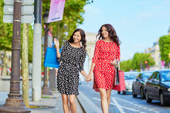 Happy twin sisters doing shopping on holidays in France Royalty Free Stock Photo