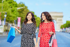 Happy twin sisters doing shopping on holidays in France Stock Photos