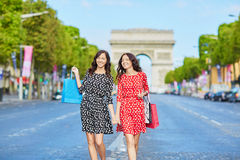 Happy twin sisters doing shopping on holidays in France Royalty Free Stock Photos