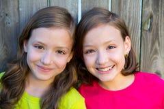 Happy twin sisters smiling on wood backyard fence Stock Photo