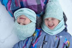 Happy twins children of little sisters girls lying on the snow a royalty free stock photography