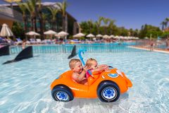 Happy twins swimming in the inflatable car royalty free stock photo