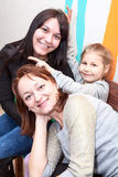 Happy two adults women and young pretty girl shooting with horns over heads. Caucasian people stock photo