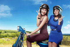 Happy two asian woman having fun riding the scoote royalty free stock photos