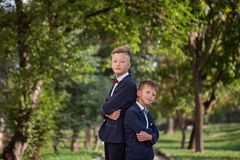 Happy two boys standing back to back on nature background in summer day stock photography