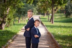 Happy two boys standing back to back on nature background in summer day stock photo