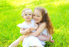 Happy two children sisters on grass in summer. Day stock photos