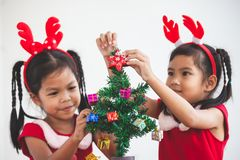 Happy two cute asian child girls decorating Christmas tree royalty free stock image