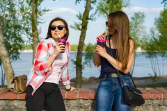 Happy two female friends drinking coffee. And having fun. Background nature, park, river. Urban lifestyle and friendship concept Stock Photography