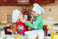 Happy family funny kids are preparing the dough, bake cookies in the kitchen. The happy two funny kids are preparing the dough, bake cookies in the kitchen Royalty Free Stock Photos