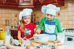 Happy family funny kids are preparing the dough, bake cookies in the kitchen Stock Photos
