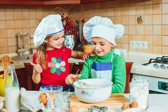 Happy family funny kids are preparing the dough, bake cookies in the kitchen Royalty Free Stock Image