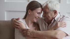 Happy loving senior father embracing young daughter looking at camera