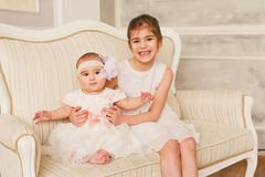 Happy two girls on the white chair Royalty Free Stock Photography