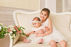 Happy two girls on the white chair Royalty Free Stock Photo