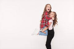 Happy two little girls sisters on white. Happy two little girls sisters screaming, rejoicing and embracing each other isolated on white background Royalty Free Stock Images