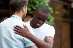 Happy two multiracial male best friends greeting embracing at meeting stock photos