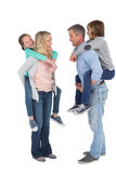Happy two parent giving their children a piggy back Royalty Free Stock Photos