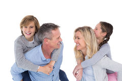 Happy two parent giving their children a piggy back Royalty Free Stock Images