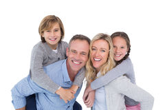 Happy two parent giving their children a piggy back Royalty Free Stock Photography