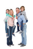 Happy two parent giving their children a piggy back Royalty Free Stock Image