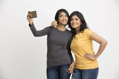 Happy two pretty young women taking selfie with mobile phone Stock Image