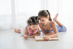 Happy two sister drawing in sketch book together at home. People lifestyle and kids play. Education and Children concept. Diverse. Ethnicities and ages royalty free stock images