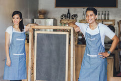 Happy two small business owner ready to open their cafe Stock Image