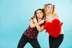 Happy two women holding heart shaped pillow Royalty Free Stock Images