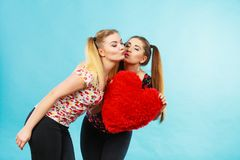 Happy two women holding heart shaped pillow royalty free stock photos