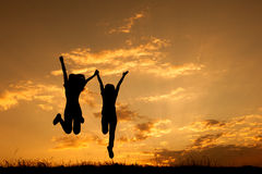 Happy of two women jumping and sunset silhouette. With copy space Stock Image