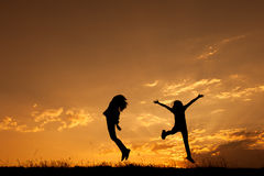 Happy of two women jumping and sunset silhouette Stock Photo
