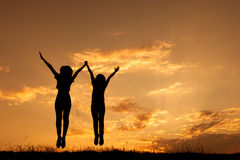Happy of two women jumping and sunset silhouette. With copy space Royalty Free Stock Images