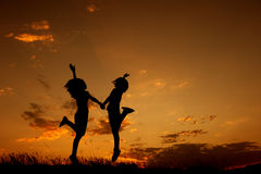 Happy of two women jumping and sunset silhouette Stock Images