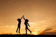 Happy of two women jumping and sunset silhouette. With copy space Stock Photography