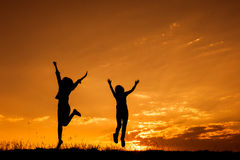 Happy of two women jumping and sunset silhouette. With copy space Royalty Free Stock Photo