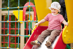 Happy two-year child on slide Stock Photos