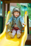 Happy two-year  girl in jacket on slide Stock Photos