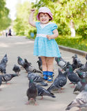 Happy two-year girl playing with doves Royalty Free Stock Image