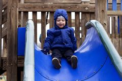 Happy two years toddler on the children`s slide. Kids playground.  Royalty Free Stock Photography