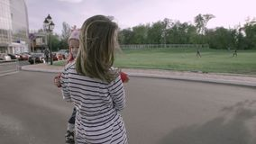 A happy two young beautiful sisters is riding a hydroskater on the road in the park. A happy two sisters is riding a hydroskater on the road in the park. The stock video footage