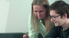 Happy two young students sitting at table and reading text message in libraly in university. Close up. Professional shot in 4K resolution. 075. You can use it stock video