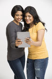 Happy two young woman using digital tablet. Happy two young women using digital tablet on white Stock Photo