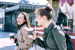 Happy two young women are smiling heavily and laughing walking the streets of the city day royalty free stock images