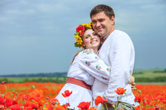 Happy ukrainian couple in blossom poppies field Stock Images