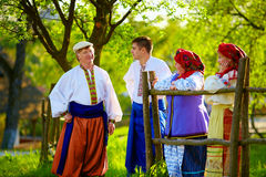 Happy ukrainian family in traditional costumes talking near the country house Stock Images
